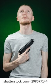 Firearms and murderer topic: suicide in a gray t-shirt holding a gun on a dark green background isolated in studio