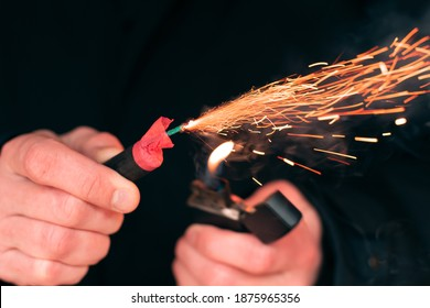 The Firecracker in a Hand. Man Holding a Burning Petard in His Hand. A Human with a Pyrotechnics that Burns with Sparks and Smoke Outdoors