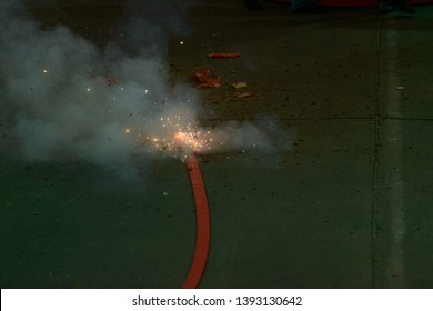 Firecrackers are tied on long fuses string on the ground, blasting. (blurred focus)
