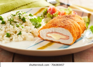 Fired cordon bleu chicken served with rice and parsley on plate
