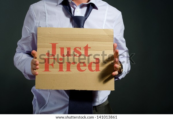 fired employee holding just fired sign in hand
