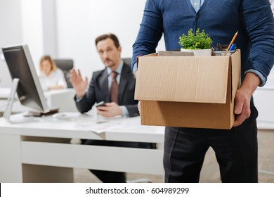 Fired senior employee leaving the office with the box