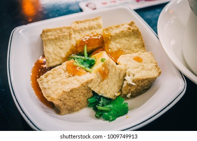 Fired Tofu with Sauce in White Dish. Chinese Traditional Deep Fried Crispy Tofu or Bean Curd served as appetizer or snack in Taipei, Taiwan, concept of healthy vegetarian food in Asia Background