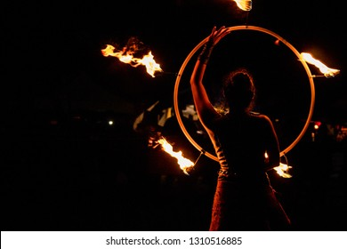 fire-eater, fire dancer with flaming hoop in night show at medieval festival with black background
