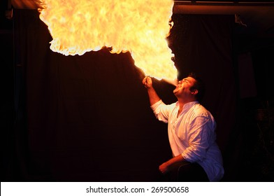 fire-eater with flame over dark background