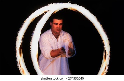 fire-eater spinning flames over dark background