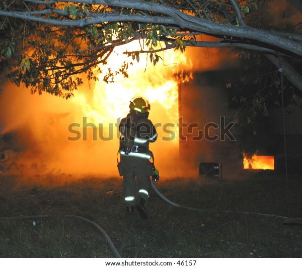 a firefighter battles a blaze at an abandoned house
