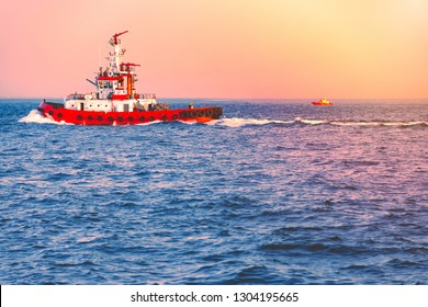 Firefighter boat at sea near Istanbul, Turkey. Blue water in foreground and sunset sky in background