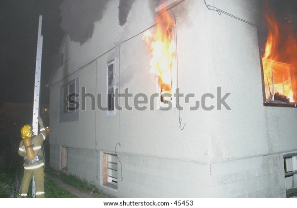 a firefighter carries a ladder to the side of a house on fire