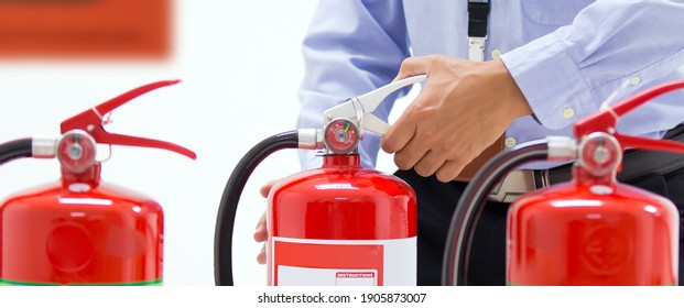 Firefighter checking the handle of the red fire extinguishers tank in the building concepts of prevent case for emergency and safety rescue and fire training.