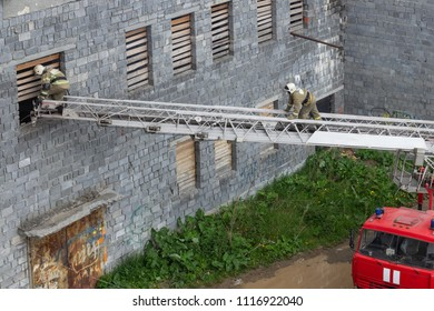 The firefighter climbs the stairs to the window of the house.