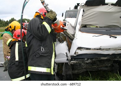 Firefighter cutting away metal to enter a wrecked car (drill)