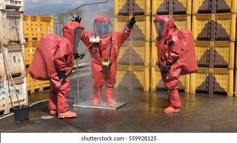 Firefighter dressing protective suit cleans up after sealing a leaking container from corrosive toxic hazardous material Ammonia in fruit factory, Yesud Hamaala, Israel, March 21, 2016.