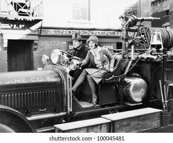 Firefighter driving a fire engine and a young woman sitting beside him