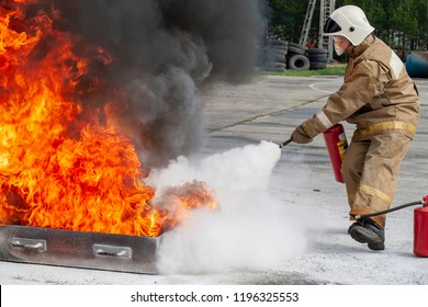 Firefighter during training with a huge fire in the brazier.