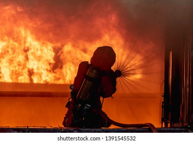 Firefighter in a  Extinguish Orange suit using extinguisher and water from hose for fire fighting, Firefighter spraying high pressure water to fire.