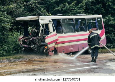 The firefighter extinguishes the water from the hosepipe road after an accident of the bus