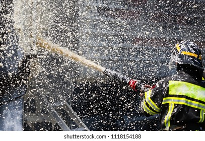 Firefighter fight with fire. Fire extinguishing foam