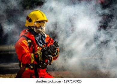 Firefighter in fire fighting operation, Firefighter spraying water in fire fighting.