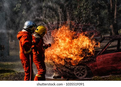 Firefighter in fire fighting suit spraying water, Firemen fighting raging fire with huge flames of burning car, Fire prevention and extinguishing concept