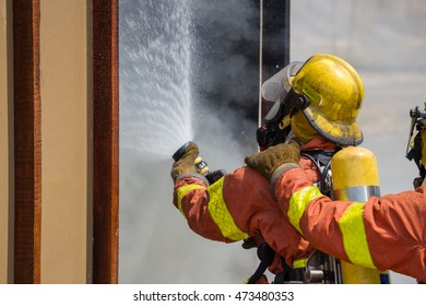 firefighter in fire protection suit spraying water to in training