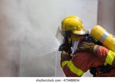 firefighter in fire protection suit spraying water to fire surround with smoke and drizzle in training