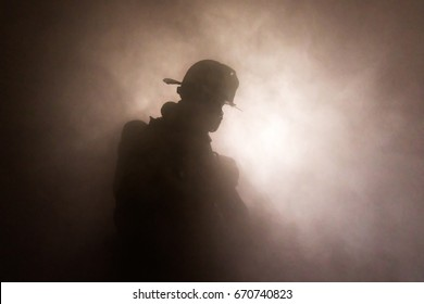 Firefighter in full turnouts silhouetted in smoke