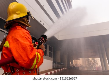 Firefighter hand holding water hose and water spraying to prevent high building.Fire fighting training.Fire man spray high pressure water to fire and copy space.