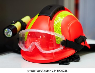 Firefighter helmet with flashlight, close-up. Construction helmet with headlamp and safety glasses