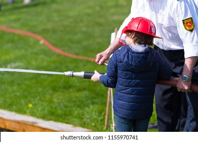 firefighter helping a young boy with a firehose during a demonstration