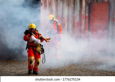 Héroe del bombero sacando a una bebé de la zona de incendio de un edificio del incendio. Rescatar a la gente de un lugar peligroso