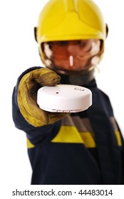 Firefighter holding fire alarm (focus on alarm) isolated on white