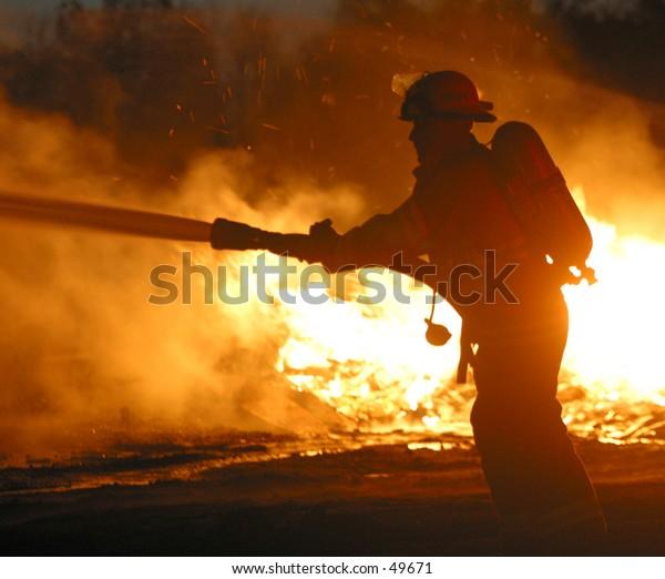 a firefighter hoses down a blaze