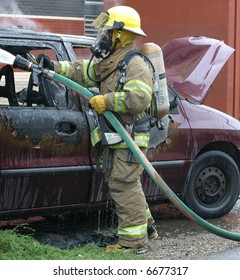 A firefighter hoses down a van which caught fire.