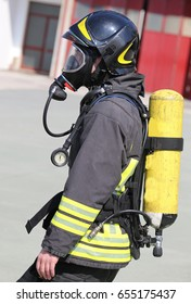 Firefighter with large yellow oxygen cylinder and automatic respirator