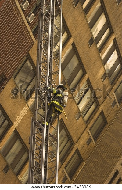 firefighter on duty in New York is using ladder to reach fire