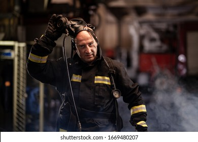 firefighter portrait wearing full equipment and emergency rescue equipment. taking off oxygen mask all sweaty after successful intervention. smoke and fire trucks in the background.