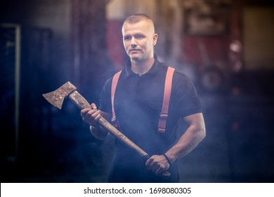 firefighter portrait wearing shirt and red throuser suspenders, holding an axe. smoke and fire trucks in the background.