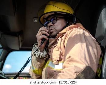 A firefighter in protective clothing and a helmet sits in a cargo rescue vehicle and talks on the radio in emergency situations.