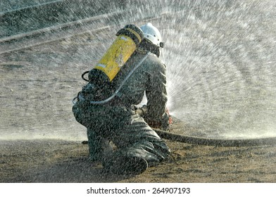 Firefighter in protective suit works with water cannon