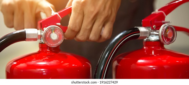 Firefighter pulling the safety pin at the handle of the red fire extinguishers tank in the building concepts of prevent case for emergency rescue and fire training.