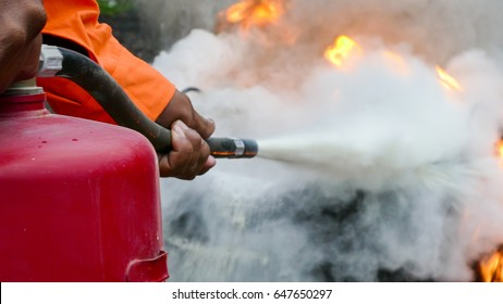 Firefighter putting out a fire with a powder type extinguisher.