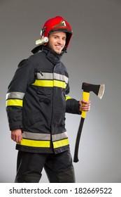Firefighter in red helmet holding axe. Three quarter length studio shot on gray background.
