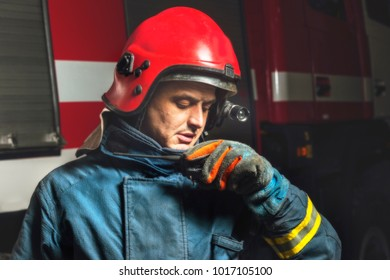 A firefighter rescue speaker speaks on a radio station in the background of a fire truck
