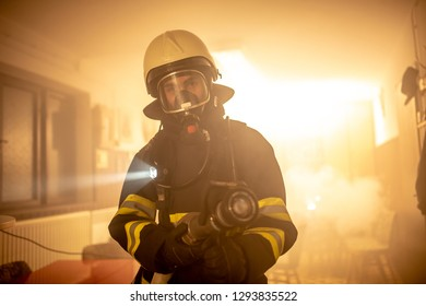 Firefighter in a room full of smoke,  checking for fire
