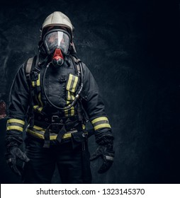 Firefighter in safety helmet and oxygen mask wearing protective clothes. Studio photo against a dark textured wall