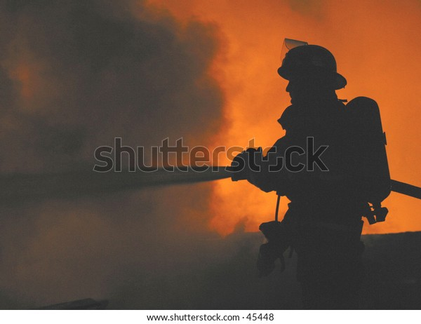 firefighter silhouetted at a fire