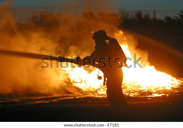 a firefighter is silhoutted against a  fire