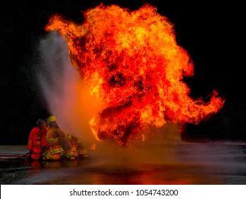 Firefighter spray water to fire on black background.