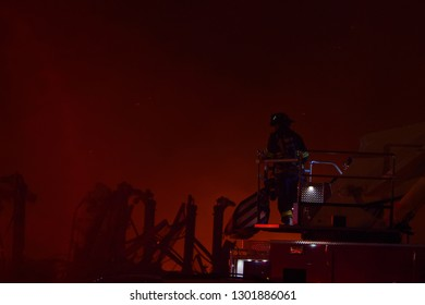 Firefighter standing on top of fire truck with large fire in the backgorund